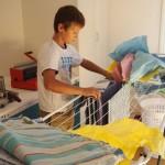 Mergim nimmt die trockene Wäsche ab.